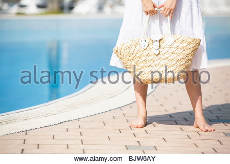 Young barefoot woman standing poolside wearing white sundress - Stock Photo