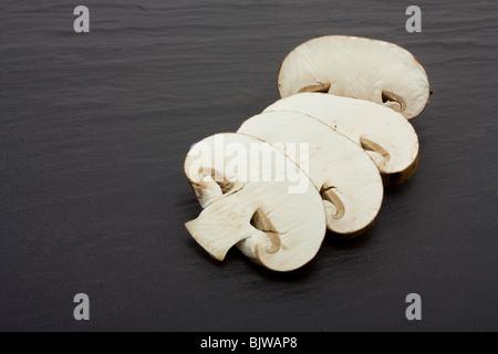 Sliced and whole Chestnut Mushrooms on background of dark slate. - Stock Photo