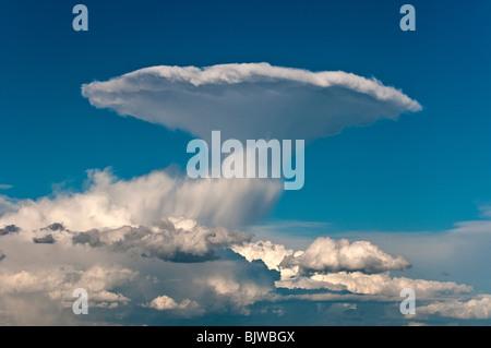 Distant thunder cloud (Cumulonimbus incus) erupting in the sky near Siena, Tuscany, Italy - Stock Photo
