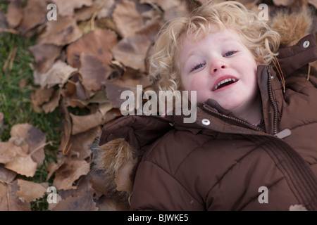 Young girl lying down on leaves - Stock Photo
