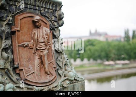 PRAGUE, Czech Republic - Communist plaque of a worker on a bridge in Prague with Prague Castle in the distance - Stock Photo
