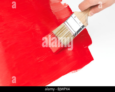 Person holding a paintbrush putting a red coat of paint over white background - Stock Photo