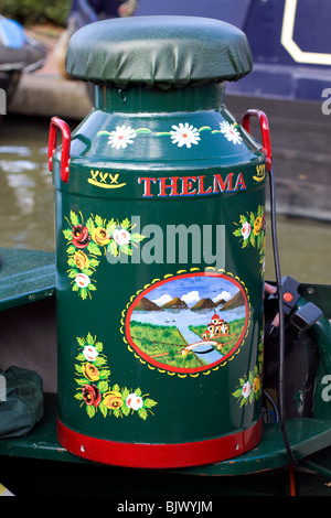 Green painted old milk churn on a canal barge - Stock Photo