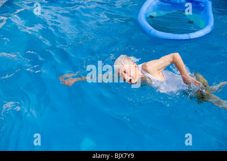 Elderly man swimming in a pool. - Stock Photo