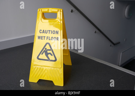 caution wet floor sign at the top of a set of stairs in a modern building - Stock Photo
