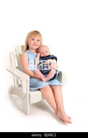 Big Sister Holding Her Newborn Baby Brother on White - Stock Photo