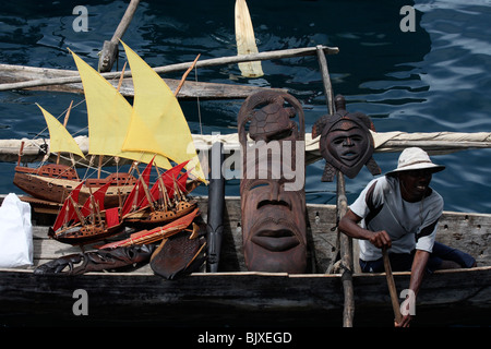 young poor african male in a boat with curios african sail boats,wooden masks and other suveniers for sale,madagascar,africa - Stock Photo