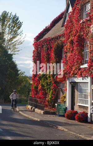 Man cycling Village Post Office Stores in autumn sunshine Acton Burnell Shropshire England UK United Kingdom GB - Stock Photo