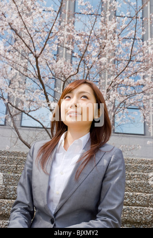 Young woman enjoying cherry blossoms - Stock Photo