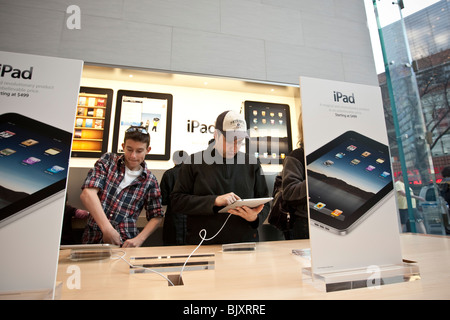 People try out the new iPad at the UWS Apple store in New York, USA, 3 April 2010. - Stock Photo