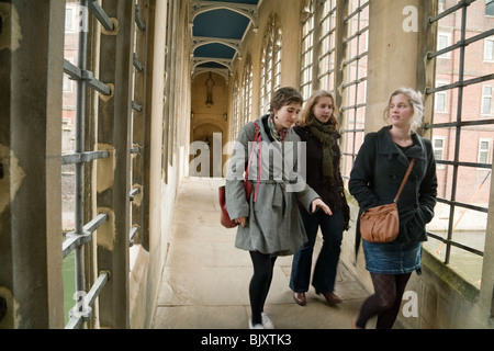 Three female students crossing the Bridge of Sighs, St Johns College, Cambridge University, Cambridge, UK - Stock Photo