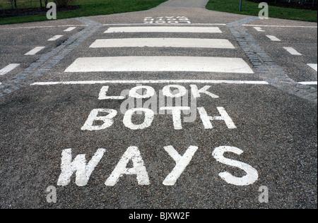 Look both ways painted road marking and zebra crossing, England UK - Stock Photo