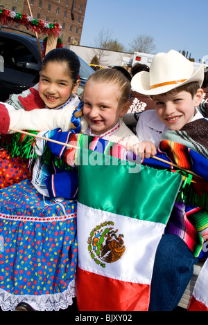 Three Hispanic and white kids in traditional Mexican clothing holding Mexican flag. Cinco de Mayo Fiesta St Paul - Stock Photo