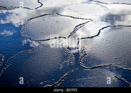 Thin ice breaking on a spring day, clouds and sky reflected in the water. - Stock Photo