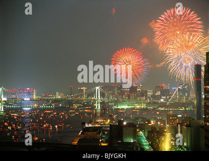 Firework display over city at night, Tokyo, Japan - Stock Photo