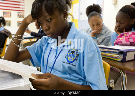 African-American high school student reads book during class - Stock Photo