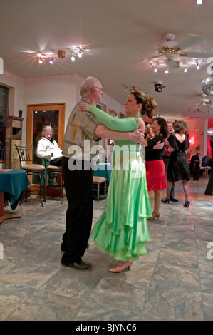 An elderly man dances a waltz with a younger woman in a green gown in ballroom style dancing to stay healthy. - Stock Photo