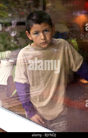 multicultural multi-cultural 9 -10 year years old Hispanic boy looking out through a window on a rainy day. Child's - Stock Photo
