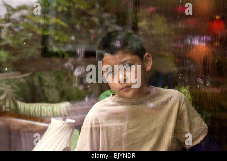 multicultural multi-cultural child 9 -10 year years old Hispanic boy looking out through a window on a rainy day.thoughtful - Stock Photo