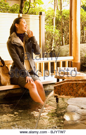 Woman talking on a mobile phone and soaking feet in hot spring - Stock Photo