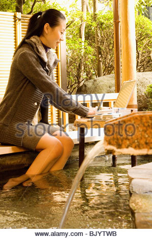 Woman on laptop and soaking feet in hot spring - Stock Photo