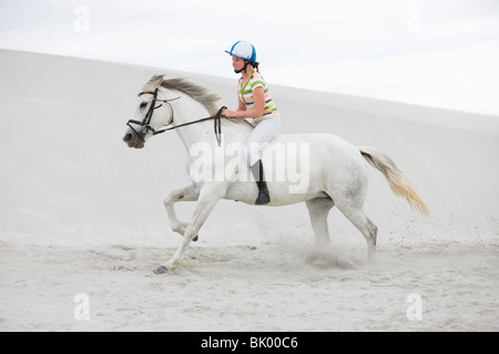 Young girl riding horse on the beach - Stock Photo