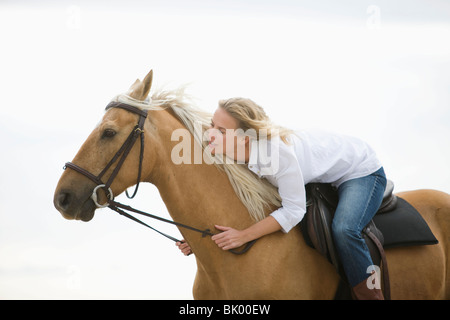 Girl with brown horse on the beach - Stock Photo