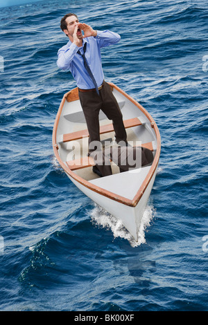 Man in a little boat crying for help - Stock Photo
