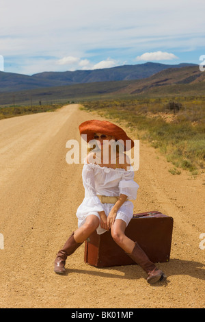 Lonely woman hitching in desert - Stock Photo