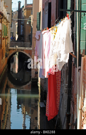 Laundry hanging up to dry over a quiet canal in Venice, Italy - Stock Photo