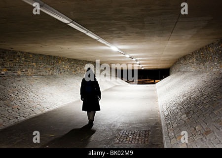Woman walking alone through underpass at night Abergavenny Wales UK - Stock Photo