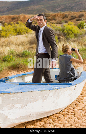 Business-couple lost in desert - Stock Photo