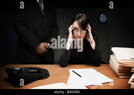 Boss behind stressed woman at desk - Stock Photo