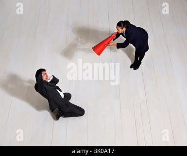 Business woman shouting at man on floor - Stock Photo