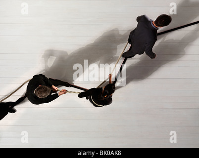 Business man leading others with rope - Stock Photo