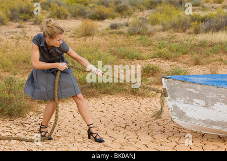 Businesswoman towing a boat - Stock Photo