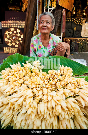 Woman selling flowers in Chatuchak Weekend Market in Bangkok, Thailand. - Stock Photo