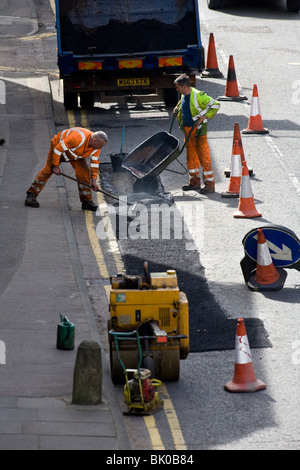Council workers repair the damaged road surface in a street in Berkhamsted, Hertfordshire UK - Stock Photo