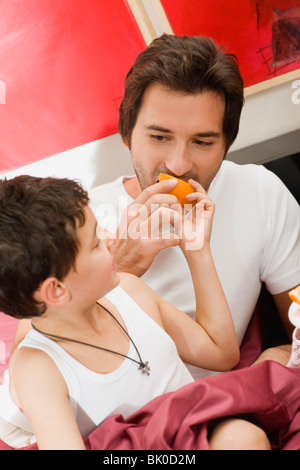 Father and son having breakfast in bed - Stock Photo