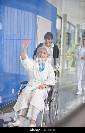 Old woman in a wheel chair and nurse - Stock Photo