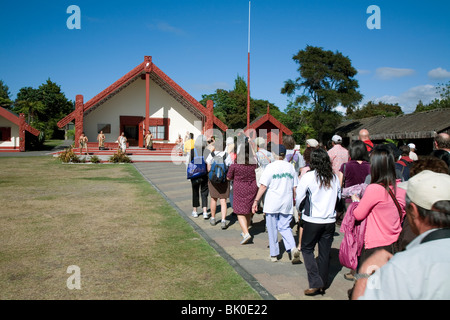 Visitors head for Rotowhio Marae meeting house for a daytime Maori cultural performance at Te Puia New Zealand - Stock Photo