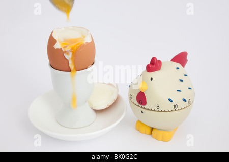 Chicken egg timer with an open soft boiled egg with runny yolk in an egg cup on a white background - Stock Photo