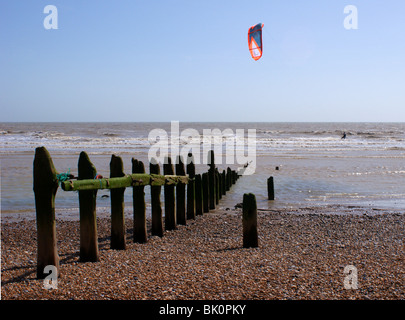 Kite Surfer using a brightly coloured kite to power him along. The upright wooden posts in the forground are old - Stock Photo