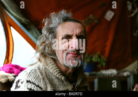 Artist Hamish McKenzie who lives aboard his houseboat on the banks of the River Adur in Shoreham-by-Sea West Sussex - Stock Photo