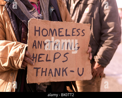 Homeless persons holding sign asking for help and handouts, unemployed and homeless the American recession is tough - Stock Photo