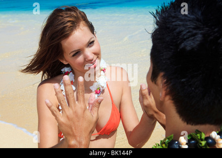 Pacific Island man and a young caucasian woman on the beach in Hawaii together and touch hands in a meditation and - Stock Photo