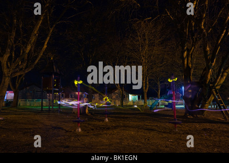 Light trails from reflexes of a child on a playground by night, long time exposure. - Stock Photo