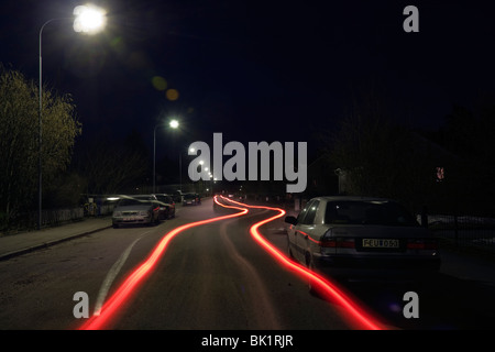 Light trails from the back of a car by night, long time exposure. - Stock Photo