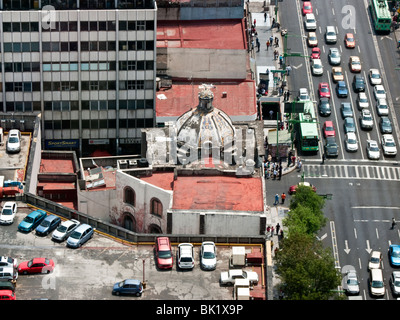 view looking down on traffic & electric buses on Avenida Laslo Cardenas & small old church sandwiched between large - Stock Photo