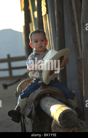 A cute 2-4 year old mixed race boy sitting on a saddle and holding a cowboy hat(Released) - Stock Photo